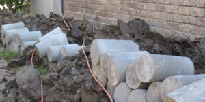 a pile of piers at a construction site for foundation repairs