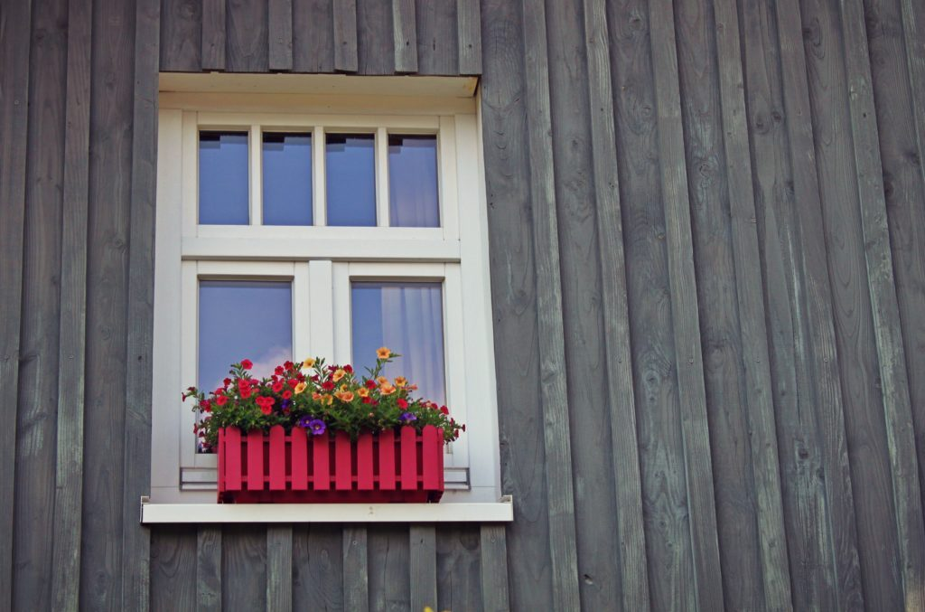 Close up of window with flowers on wood-covered home