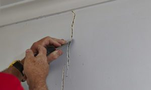 man repairing cracked drywall